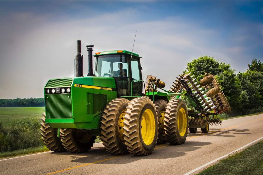 John Deere 8760 farm tractor with a folded farm tractor disc attached driving down a country road in Indiana.
